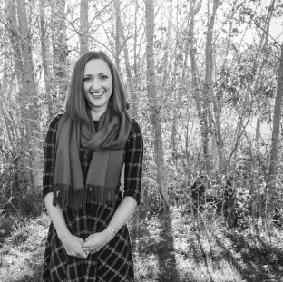 Headshot, Sophia smiling in front of trees, black and white, fall leaves and shadows.